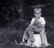 Sad little boy with teddy bear black and white. Little boy sitting on a prop holding his teddy bear, looking sad and lonely Stock Images