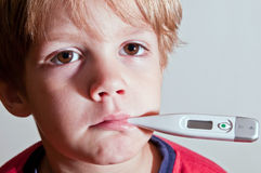 Sad little boy with thermometer Stock Image