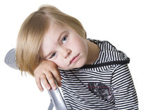 Sad little boy. Young boy wearing striped shirt and hood looking at the camera Royalty Free Stock Photo