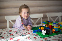 Sad little Caucasian girl  playing constructor on table Stock Photo
