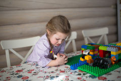 Sad little Caucasian girl  playing constructor on table Royalty Free Stock Photography