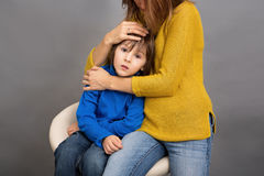 Sad little child, boy, hugging his mother at home, imag. E, copy space. Family concept Royalty Free Stock Image