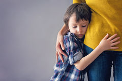 Sad little child, boy, hugging his mother at home Stock Image