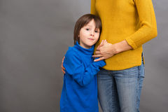 Sad little child, boy, hugging his mother at home, isolated imag Stock Image