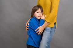 Sad little child, boy, hugging his mother at home, isolated imag Royalty Free Stock Images