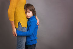 Sad little child, boy, hugging his mother at home, isolated imag Stock Images