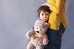 Sad little child, boy, hugging his mother at home Stock Images