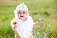 Sad little child with flower on green field Royalty Free Stock Images