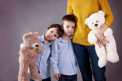 Sad little children, boys, hugging their mother at home, isolate. Sad little children, boys, hugging their mother at home,  image, copy space. Family concept Royalty Free Stock Image