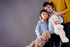 Sad little children, boys, hugging their mother at home, isolate. D image, copy space. Family concept Royalty Free Stock Photo