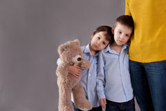 Sad little children, boys, hugging their mother at home, isolate. D image, copy space. Family concept Stock Photo