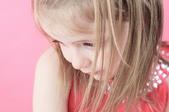 A sad little doll girl in pink background Royalty Free Stock Images