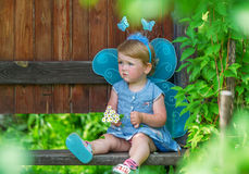 The sad little fairy in a blue dress with bouquet of white daisies. Stock Image