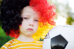 Sad little german child crying over her national football team's loss Stock Photo