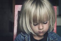 Sad little girl. A serious looking girl sitting on a chair looking away from the camera Royalty Free Stock Images