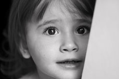 Sad little girl. Little girl with eyes full of scare and sadness Stock Image