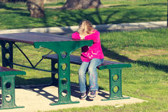 Sad little girl. A sad little girl hiding her head in her hands in a park stock images