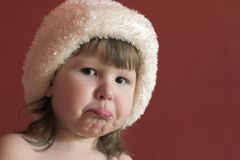Sad Little girl. In white hat looking at you Royalty Free Stock Images