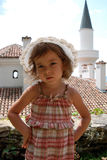 Sad little girl. A cute little caucasian girl in summer clothes with sad facial expression standing in front of the Balcic castle in Bulgaria stock image