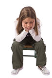 A sad little girl. Young girl looking sad while sitting on a chair Stock Photos