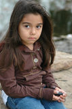 Sad Little Girl. Sitting on a rock in a park Royalty Free Stock Image