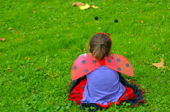 Sad little girl age 05 dressed up as lady bug Royalty Free Stock Images