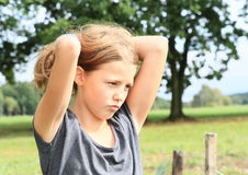 Sad little girl. Sad or angry little kid - young brunette girl in grey t-shirt Stock Images