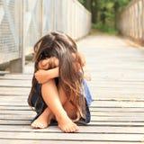 Sad little girl. Sad barefoot girl with long hair in blue skirt sitting wooden bridge Stock Photo