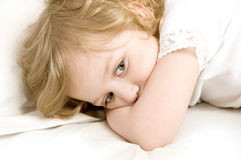 Sad little girl in the bed close-up stock image