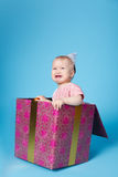Sad little girl with birthday cap sitting in gift. Unhappy little girl with birthday cap sitting in gift box Royalty Free Stock Photography
