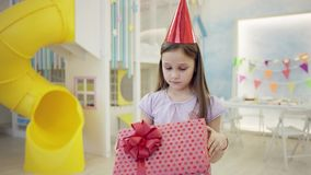 Sad little girl in a birthday hat looking at her present box in front of the camera. In a playroom stock video