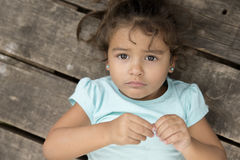 Sad little girl in blue t-shirt lying over wooden background Stock Images