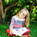 Sad little girl with a book in a park Royalty Free Stock Photography