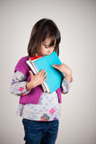 Sad little girl with books Royalty Free Stock Image