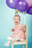 Sad little girl with cap and balloons. Unhappy little girl with cap and balloons Stock Photography