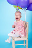 Sad little girl with cap and balloons. Unhappy little girl with cap and balloons Stock Photos