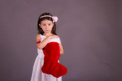 Sad little girl with Christmas stocking Stock Image