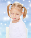 Sad little girl. The concept of celebrating the New year, Holy Christmas, or child's birthday on a blue background and white snowflakes.Distressed small, blonde Royalty Free Stock Photo