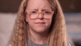 Sad little girl with confused expression. Closeup facial expression of upset little girl looking at camera. Sad little teen girl in glasses with amazing blonde stock video