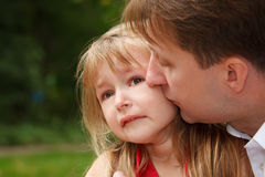 Sad little girl cries in park. Father calms her. Kissing on cheek.  Close up Royalty Free Stock Photo