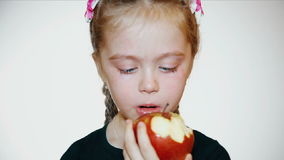 Sad little girl eats a red apple stock video footage