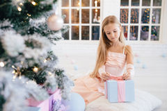 Sad little girl in an elegant pink dress holding gift box near Christmas tree Stock Photo