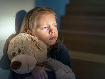 Sad little girl embracing her teddy bear - feels lonely Stock Images