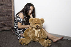 Sad little girl embracing her teddy bear. punished girl sitting near white wall Stock Photos