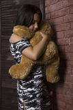 Sad little girl embracing her teddy bear. punished girl standing near brick wall Stock Photo