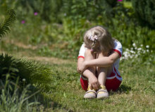 Sad little girl in garden. A sad little girl sitting on grass in a garden, looking away royalty free stock photos