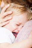 Sad little girl on hands. Mom soothing baby daughter in her arms Royalty Free Stock Photo