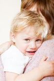Sad little girl on hands at mom. Mom soothing baby daughter in her arms Stock Images
