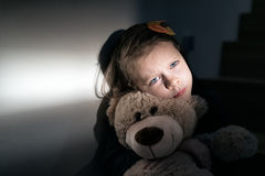 Sad little girl holding her teddy bear. She feels lonely Royalty Free Stock Photos