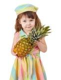 Sad little girl holding large pineapple Royalty Free Stock Photography